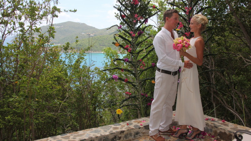 Tropical flowers woven by hand into the palm leaves behind the bride and groom - Josiah's Bay and Stoney Bay Pointe in the background